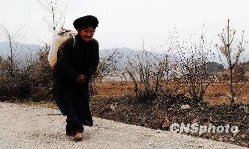 3月26日,贵州威宁县板底乡一位71岁的彝族老人徒步背水回家。据了解,由于2009年下半年以来的干旱影响,近半年时间老人都是从山下背水回家使用。
