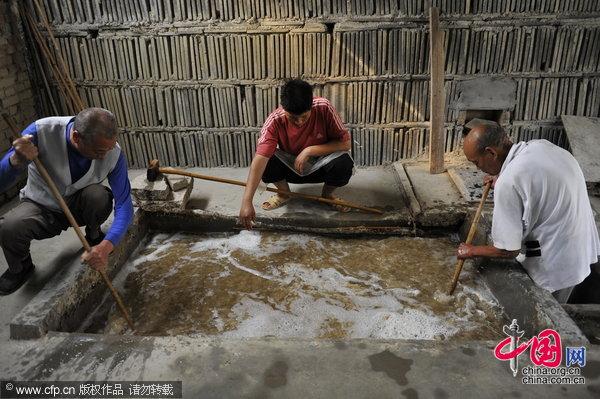 将切碎并洗净的树皮纤维彻底打碎,放入特制的池水中充分搅匀,一池纸浆