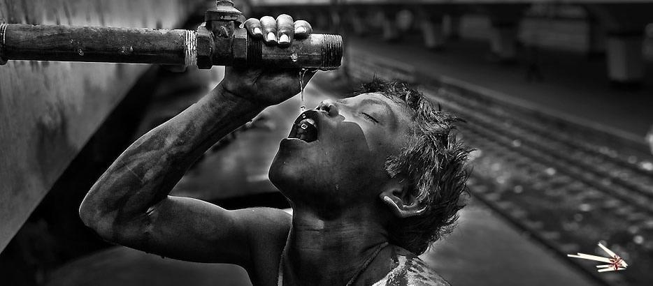 由于贫困,人们喝不上干净的水。Khaled,这个十三岁的少年,正在火车边上接一根管子里水喝。这根从火车车顶延伸下来的水管专门为车厢提供饮用水。孟加拉国摄影师Ismail Ferdous 于 2011年4月5日 摄于 孟加拉国达卡的卡马拉普火车站。