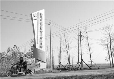 12月10日,一辆农用三轮车从宿州市埇桥区帝元现代农业门前驶过。10月,全国首单农地经营权流转信托计划落户埇桥区,区政府把5400亩地委托中信信托,信托公司再委托帝元农业作为第三方运营土地。A14-A15版摄影/新京报记者 刘刚