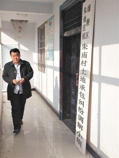 12月9日,宿州朱仙庄镇朱庙村支书沈加亮从该村土地流转机构——土地承包纠纷调解小组门牌前走过。