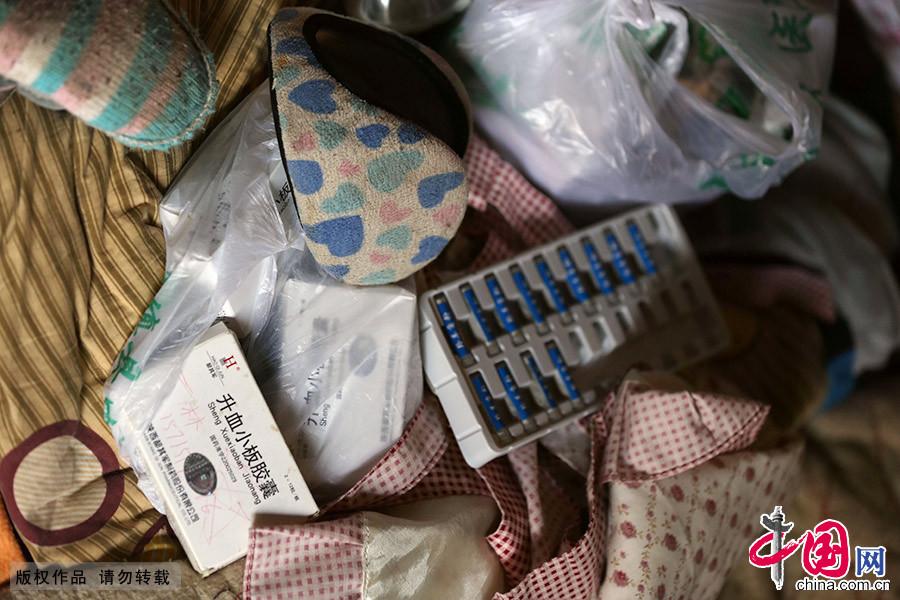 家里的床上,散落的摆放着小雨林吃的药。因为没有多余的钱进行住院或者系统地治疗,小雨林只能吃一点中药和西药维持现状。中国网图片库 李斌/摄