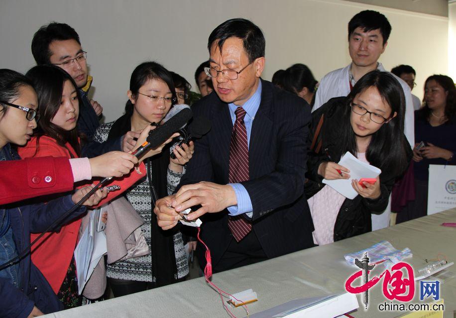 王中林院士为媒体记者们演示摩擦发电机的最新研究成果。