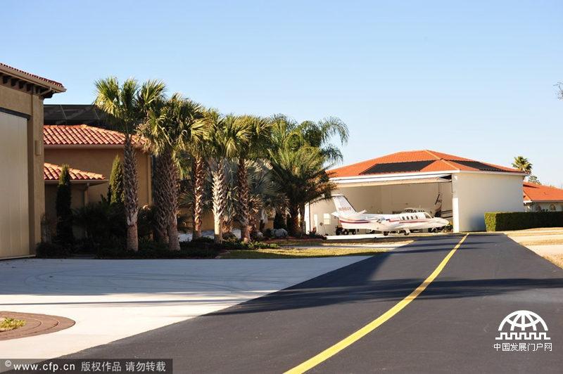 中国发展门户网讯 5月8日消息(具体拍摄时间不详),在美国佛罗里达州一片风景优美、安静隐秘的别墅住宅区内,坐落着风格各异的房屋,而每一栋房屋门前都停放着1架或1架以上的飞机。房屋门前的大道整齐宽阔,并直通毗邻小区的一条修葺完整的飞机跑道,跑道上不时地会有飞机起飞或降落。而这些飞机几乎都是这片别墅小区业主们的私人座驾,业主们每天就是这样从自家门前驶出飞机,在这条跑道起飞后飞往其目的地,返程后亦在这里降落,返回自己的家。这里就是美国最著名的航空小镇Spruce Creek的日常生活场景。Spruce Cre
