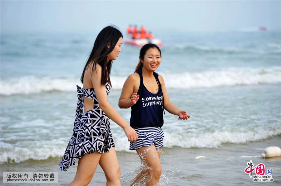 2016年7月14日,山东青岛金沙滩海水浴场,游客在海水中享受清凉.