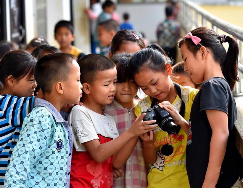 """弄勇小学""""摄影梦想社""""学生浏览刘顺媛(右二)拍摄照片"""