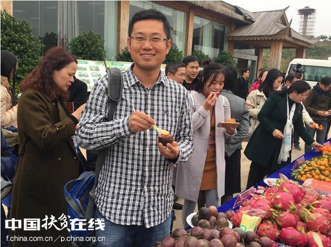 图为村民邀请媒体记者品尝村民自己种的水果 王东海摄影