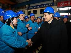 Chinese President Hu Jintao (R Front) shakes hands with a woman as he visits workers and inspects production at Dongfang Steam Turbine Works in Hanwang Township of Mianzhu City, southwest China's Sichuan Province, December 28, 2008. President Hu Jintao visited quake-hit Sichuan Province on December 27-29, showing concern for survivors and inspecting reconstruction work. [Xinhua]