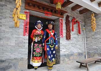 Bridegroom Tang Zhiguo (R) and his bride walk to attend wedding at the Jina Qiang Ethnic Minority Village of Beichuan County, southwest China's Sichuan Province, on April 26, 2009. Twenty new couples held group wedding on Sunday.