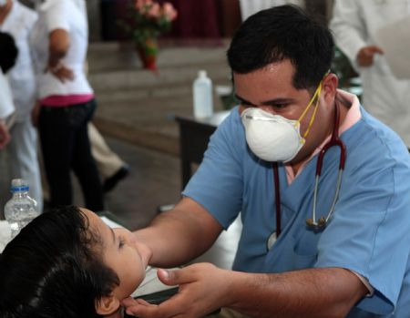 A doctor checks the conditions of a boy who has close contact to the first A/H1N1 flu case at a children's hospital in Managua, capital of Nicaragua, on June 2, 2009. The condition of the first A/H1N1 flu case in the country remains stable, and the persons who have close contact to her are being checked to eliminate the possible spread of the flu.