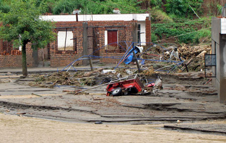 Photo taken on July 27, 2009 shows the scene after the mudslide hit Shuitang Village, Panlian Town of Miyi County, southwest China's Sichuan Province. Twenty-two people are dead and seven missing after torrential rains triggered floods in Miyi County, local authorities said Monday.