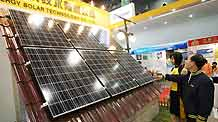 Visitors watch a building-top solar power system at the 2009 Hangzhou International Recycling Economy and Environmental Industry Expo of China in Hangzhou, east China's Zhejiang Province, October 31, 2009.
