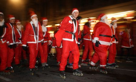 Roller skaters dressed as Santa Clause skate along the streets during the Santa Skate in London, capital of Britain, on December 19, 2009.