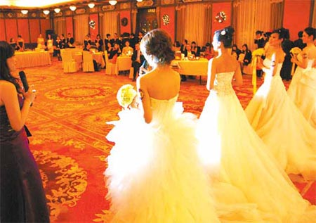 Female models show off wedding dresses at a dating party for the wealthy.