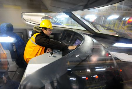 A worker checks in the control room of a high-speed train at the high-speed railway maintenance base in Wuhan, capital of central China's Hubei Province, December 22, 2009.