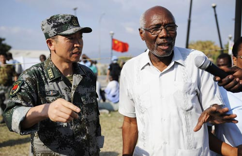 The delegate of Haiti's Health Department Roc Magloire (R) talks with the leader of Chinese medical team Liu Wendou during his visit at the clinic set up by the Chinese medical team in Port-au-Prince, capital of Haiti, on February 3, 2010.