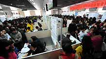 University students ask for information from recruiters during a job fair designed for the female job applicants in Nanjing, capital of east China's Jiangsu Province, March 7, 2010.