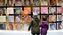 Local citizens admire an exhibition on female portrait oil painting works at downtown Nanjing, east China's Jiangsu Province, March 7, 2010.