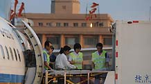 Staff members prepare to carry injured passengers out of a plane at the airport in Beijing, capital of China, Aug. 27, 2010. Ten injured passengers of Yichun plane crash incident were sent to Beijing to receive further medical treatment on Friday.