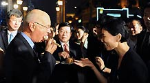 Klaus Schwab (1st L), founder and executive chairman of World Economic Forum, tastes a steamed stuffed bun at the cultural soiree of the World Economic Forum (WEF) Annual Meeting of the New Champions 2010, held at Italian style town of north China's Tianjin Municipality on Sept. 14, 2010.