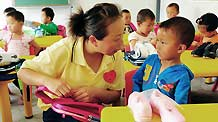 A teacher talks to a kid at a newly-built kindergarten for victims of mudslide-hit Zhouqu in Gansu Province on September 14, 2010.