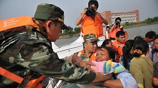 Soldiers evacuate the residents as Typhoon Megi, possibly the strongest to hit China this year, draws near, in Zhongshan, south China's Guangdong Province, Oct. 21, 2010. The typhoon is forecast to land somewhere between Huilai in south China's Guangdong Province and Xiamen of Fujian Province on Saturday.