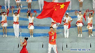 Chinese basketball player Wang Zhizhi holds the national flag at the closing ceremony of the 16th Asian Games held at the Haixinsha Island in Guangzhou, south China's Guangdong Province, on Nov. 27, 2010.