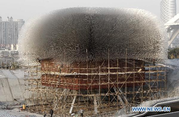 Workers take off the acrylic rods of the UK Pavilion in the World Expo Park in Shanghai, east China, Dec. 8, 2010.