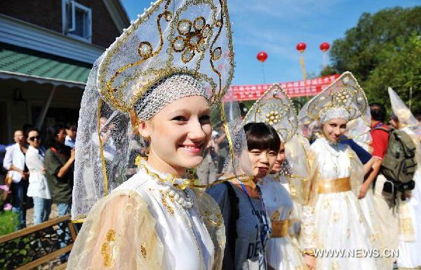 A visitor poses for photos with Russian actresses during a China-Russia cultural festival in Heihe City, northeast China's Heilongjiang Province, Aug. 23, 2011.