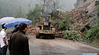 Heavy equipments are seen working to clear up the road blocked by landslides in Qinghua Township of Wanyuan, southwest China's Sichuan Province, Sept. 14, 2011.