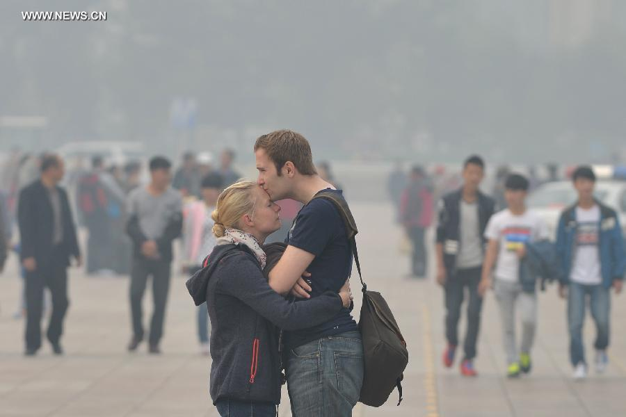 A foreign couple hug each other at the smog-shrouded Tian'anmen Square in Beijing, capital of China, Oct. 9, 2014.