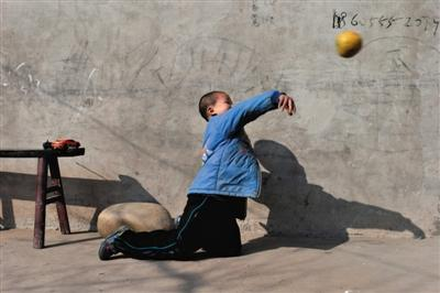 Kunkun, an 8-year-old boy with HIV in Shufangya, Sichuan province, plays at home on December 19, 2014.[Photo/The Beijing News]