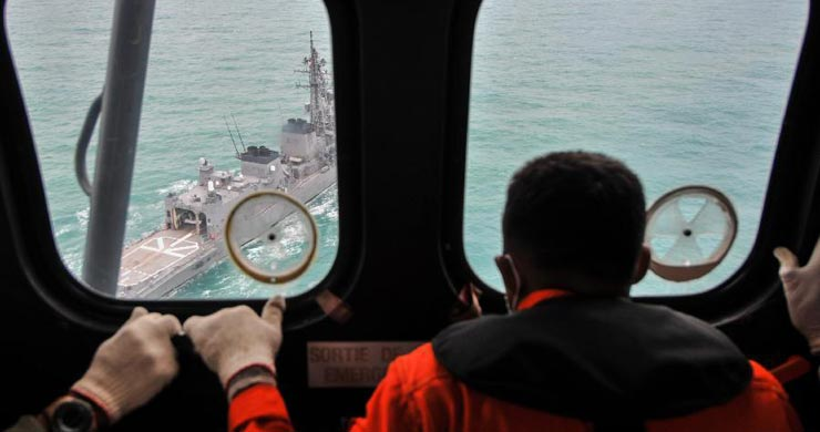 Photo taken on Jan. 6, 2015 shows a man watching a Malaysia warship during the searching of debris and victims of AirAsia flight QZ8501 at Karimata strait, Indonesia, Jan. 6, 2015. The head of Indonesia's rescue agency said the search operation would spread slightly eastward on Tuesday as the weather and currents drag wreckage in that direction.