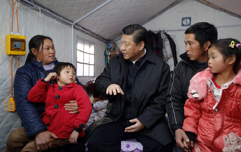 Chinese President Xi Jinping (C) pays a visit to a family affected by the 6.5 magnitude earthquake in August last year in Ganjiazhai Village, Ludian County, southwest China's Yunnan Province on Jan 19, 2015. A temporary camp was set up in the village for those displaced by the quake. [Photo: Xinhua]