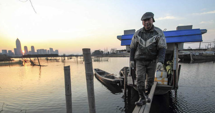 A fisherman, over 60 years old, who have fish farming for 18 years and rent 88 mu water area, returns home in the sunset, at Didang Lake of Shaoxing City, Zhejiang Province.