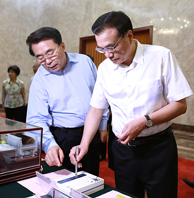 Premier Li Keqiang, accompanied by Bai Chunli, president of the Chinese Academy of Sciences, tries an electronic pen developed by the academy before sitting down for talks with leading scientists on the country's development of science. [Photo by Feng Yongbin/China Daily]