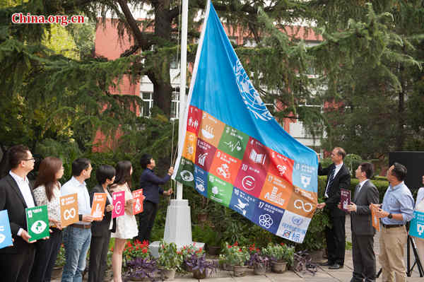 UNDP Deputy Country Director in China Patrick Haverman (R3) and Li Xi (R4) hoist a special UN flag attached to one featuring all the 17 SDGs on Wednesday, Sept. 16, 2015 in Beijing. [Photo by Chen Boyuan / China.org.cn]