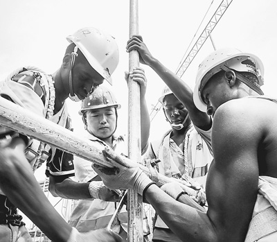 Chinese engineer Zhang Qingchun and Kenyan workers work at the Mombasa West Station. [People's Daily]