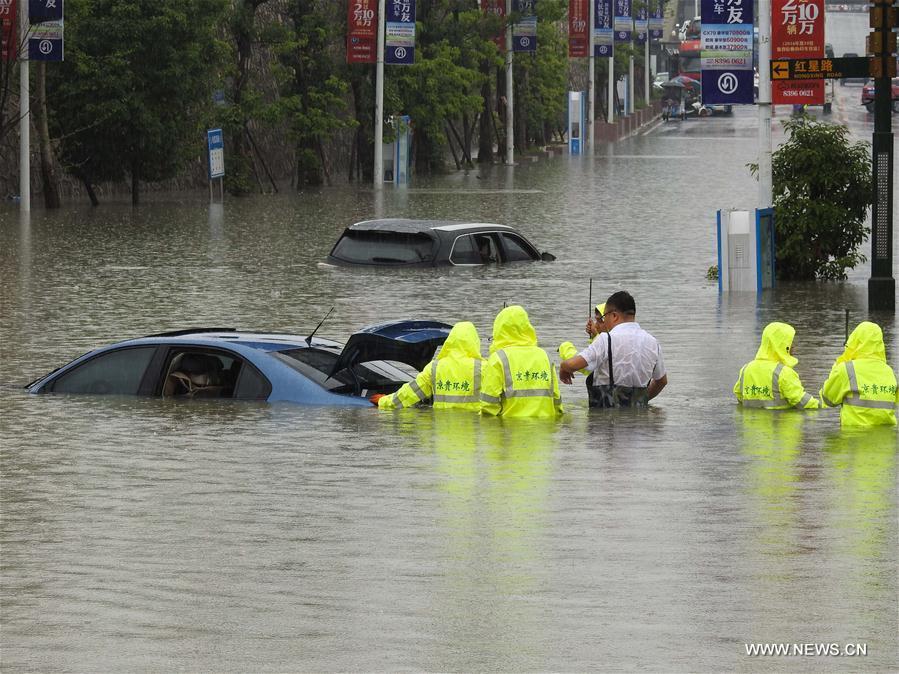 People move a car on a flooded street in Guiyang City, capital of southwest China's Guizhou Province, June 12, 2017. Heavy rain hit Guizhou since Sunday.(Xinhua/Zhang Hui)