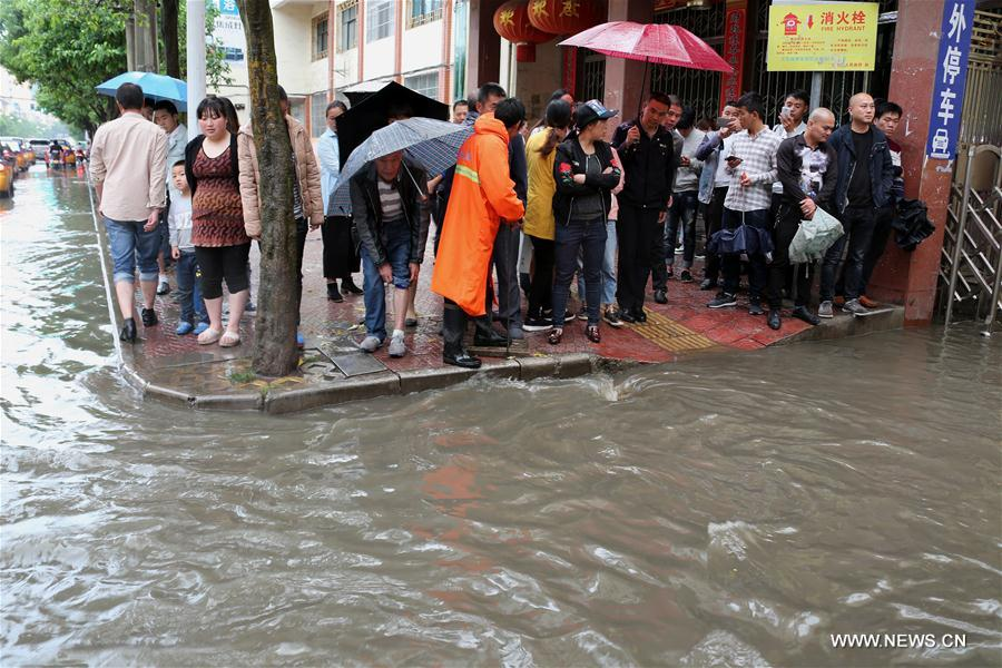 People stand by a flooded street in Weining County, southwest China's Guizhou Province, June 11, 2017. Heavy rain hit Guizhou since Sunday.(Xinhua/He Huan)
